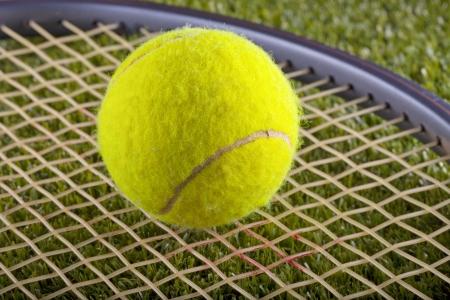 Yellow tennis ball over a racket on a green grass field