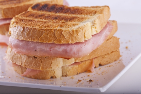 Close up of a toast with ham over a white plate