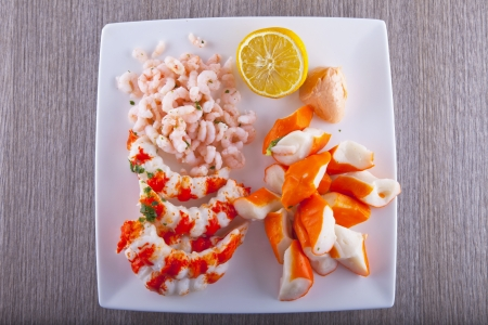 Shrimps and surimi over a white plate with lemon photo