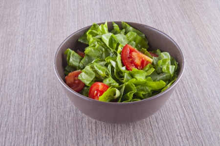 Brown cup of salad with tomatoes and lettuce photo