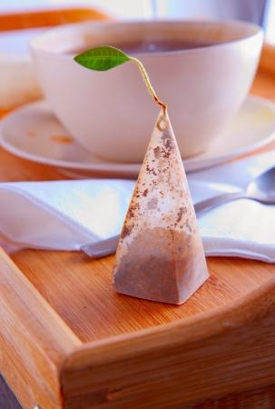 tea filter: Pyramidal tea filter over a wooden tray Stock Photo