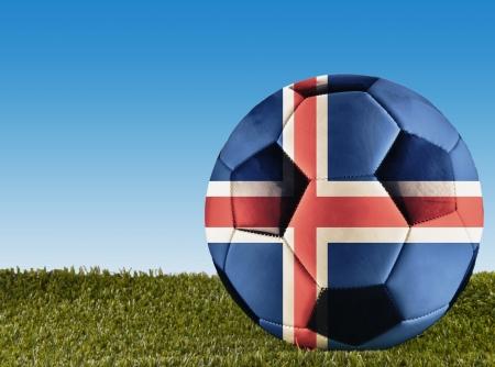 icelandic flag: Una pelota de f�tbol sobre la hierba decorado con la bandera de Islandia