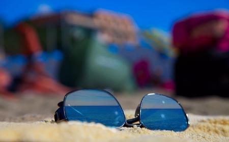 Sunglasses over a towel reflecting the sea photo