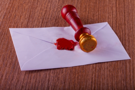 Sealing wax stamp on a letter, over wooden table photo