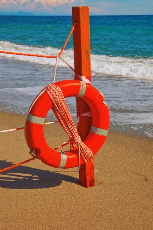 Life preserver hanging from a fence on a beach photo