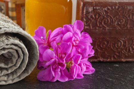 Brown soap, flower, oil and towel over stone background Stock Photo