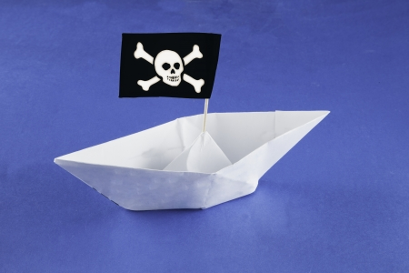 Paper pirate ship with flag over blue paper sea photo