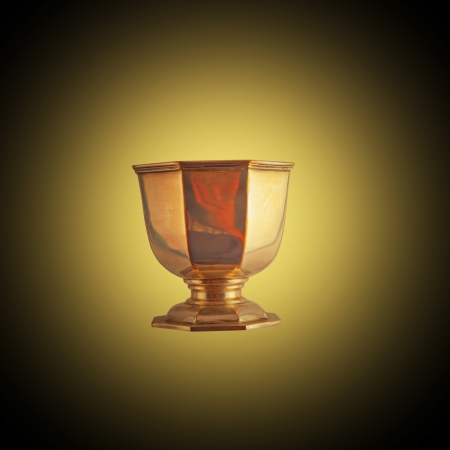 Golden cup mimic of Holy Grail over golden and black background photo