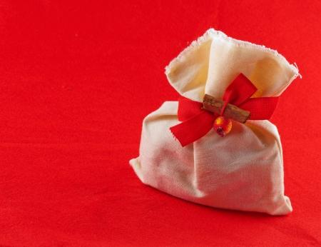 velvet ribbon: Christmas sack with decoration over red background