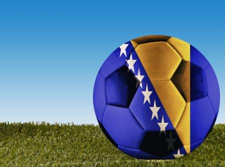 bosnian: A football over grass decorated with Bosnia Herzegovina flag