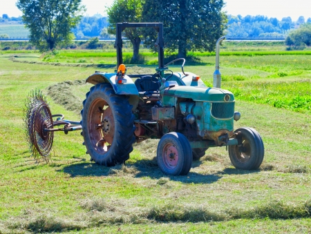 deere: Old green tractor with harrow wheel on a field Stock Photo
