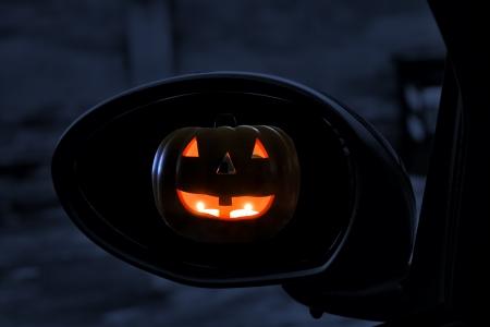 Jack-o-Lantern seen in rearviewmirror of a car Stock Photo