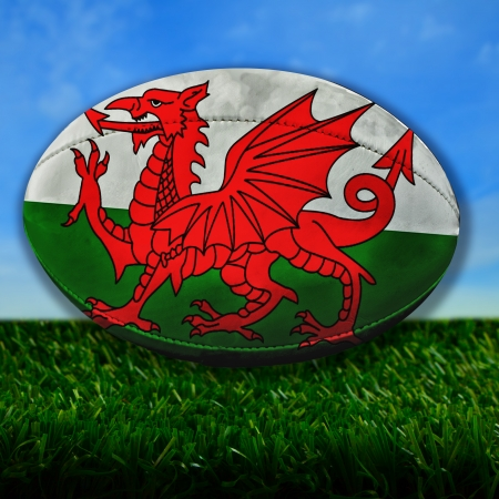 Rugby ball with Wales flag over grass Stock Photo