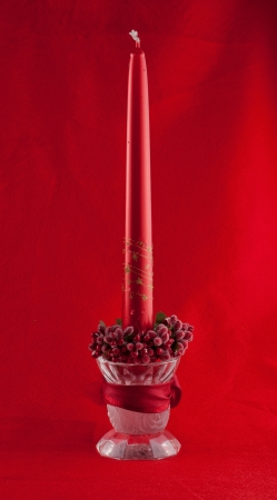 Red Christmas candle over complete red background photo