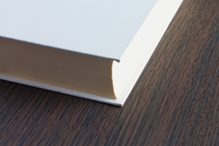 White covered book over a wooden table in closeup photo