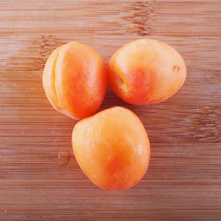 Three apricots over a lite wooden background photo
