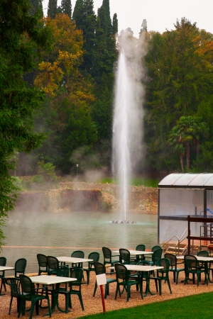 Green tables and chairs near a thermal lake  photo