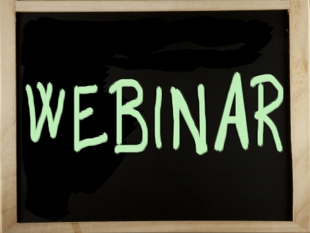 Blackboard with wooden frame with the word webinar written with green chalk photo
