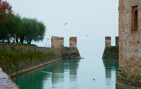 sirmione: Beautiful castle of Sirmione, Italy, extending over the lake, with many flying seagulls