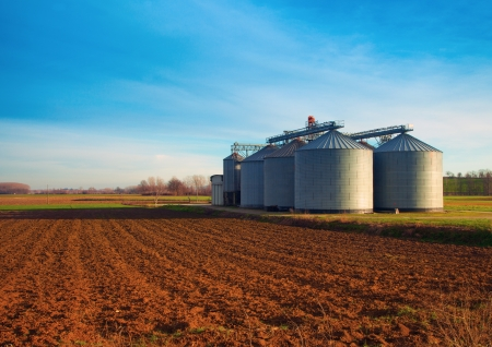storage bin: Industrial silos in the fields, in the sunset