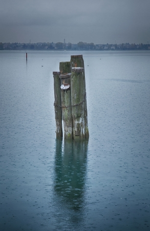 Poles in the middle of a lake under the rain Stock Photo
