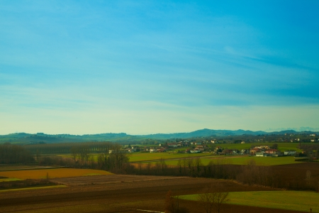 Landscape of fields under blue sky with far mountains