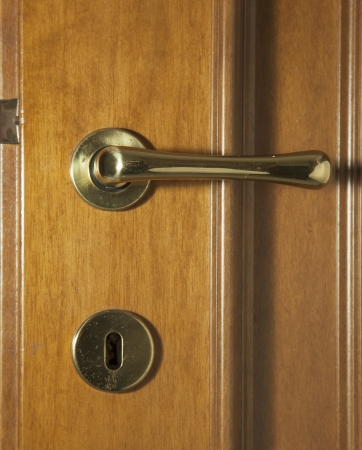 Wooden door with golden handle and keyhole photo