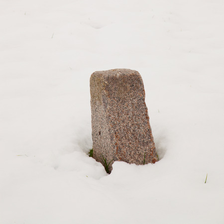 A milestone in the completely white snow photo