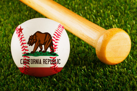 california flag: Baseball with California flag and bat over a background of green grass