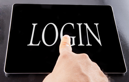 Male hand pointing to word 'Login' over black tablet photo