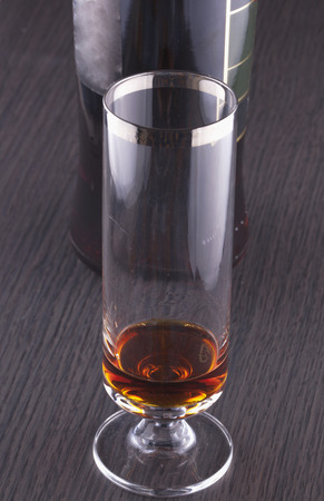 Glass of liquor with bottle on the back, over wooden table photo