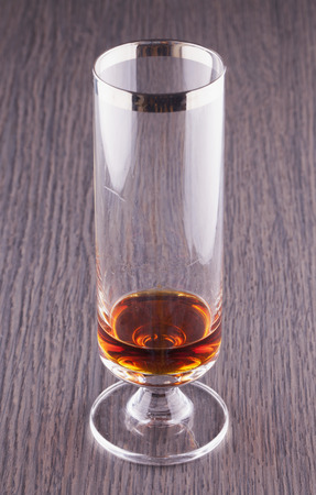 A glass of liquor over a wooden table photo