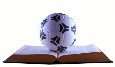 Soccer ball over book, isolated over white