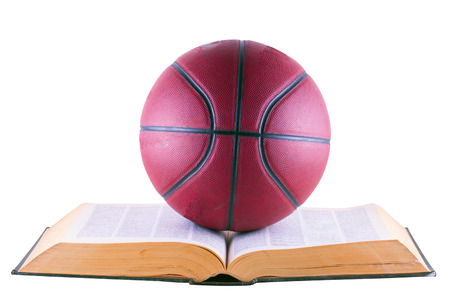 Basketball over book, isolated over white background