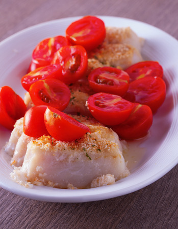 hake: Hake au gratin with tomatoes over white plate