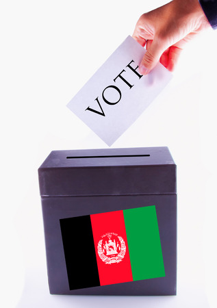 Urn for vote, with male hand posting vote and Afghanistan banner photo