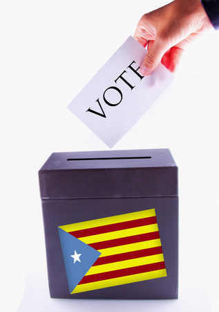 Urn for vote, with male hand posting vote and Catalunya banner photo