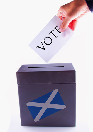 Urn for vote, with male hand posting vote and Scotland banner photo