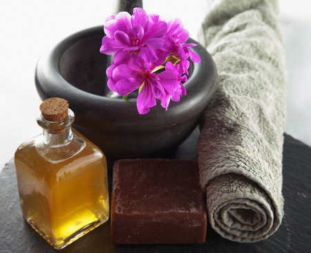 Brown soap, oil and other beauty objects over black stone
