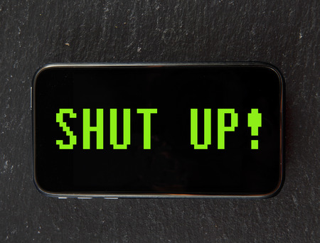Smartphone with text Shut up in vintage computer font photo