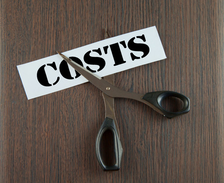 Scissors cutting the word Costs written on a paper strip, over wooden background photo