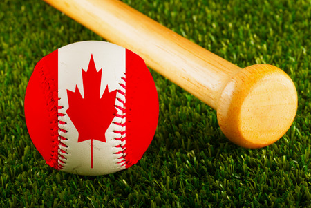 baseball stuff: Baseball with Canada flag and bat over a background of green grass