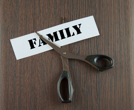 Scissors cutting the word family written on a paper strip, over wooden background photo