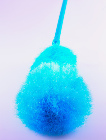 Blue feather duster in close up, gray background photo