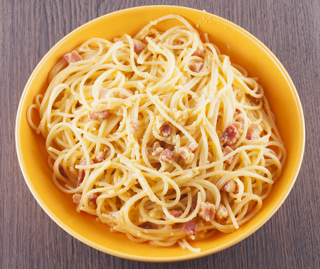 Spaghetti alla carbonara in yellow plate, wooden table