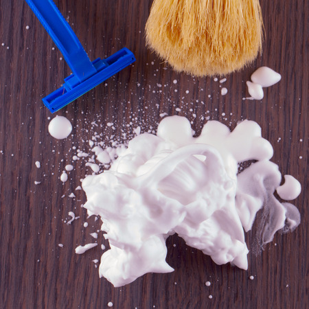 Shaving foam over wooden table, with razor and brush on the back