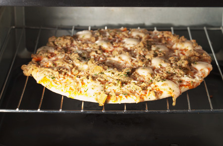 A pizza with tuna warming in an electric oven