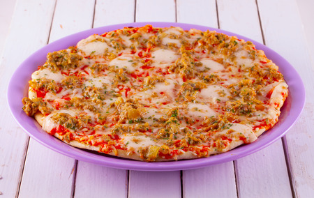 Entire view of pizza over purple plate, white wooden table