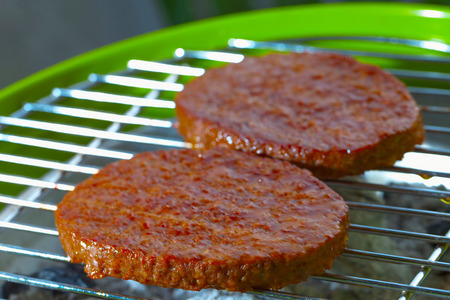 Hamburgers over a bbq, focus over low part of first hamburger