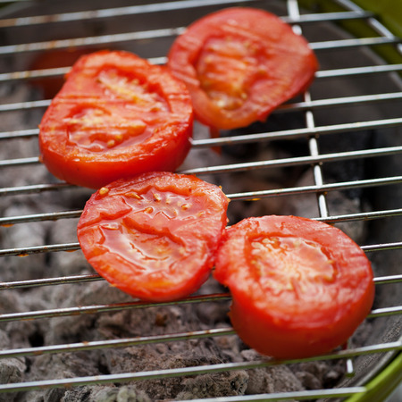 Tomatoes over metallic barbeque grill, close up Stock Photo